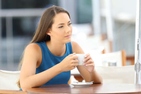 Single pensive woman alone holding a coffee mug sitting in a bar