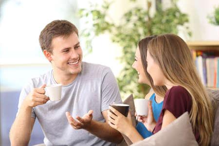 집에서 소파에 앉아 이야기하는 세 쾌활 한 친구 스톡 콘텐츠