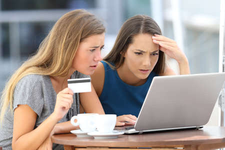 Two worried women having problems buying on line with a laptop and credit card sitting in a bar Stock fotó