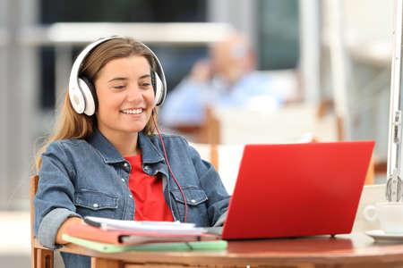 Estudiante feliz relajarse mirando contenido en línea con una computadora portátil roja sentado en una terraza de la barra