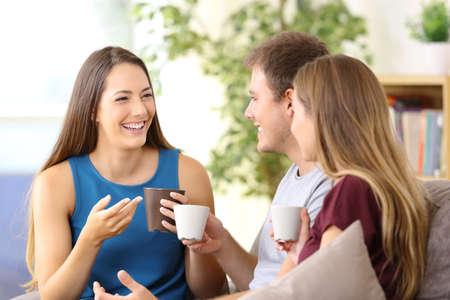 Drie gelukkige vrienden praten en drinken koffie zittend op een bank thuis