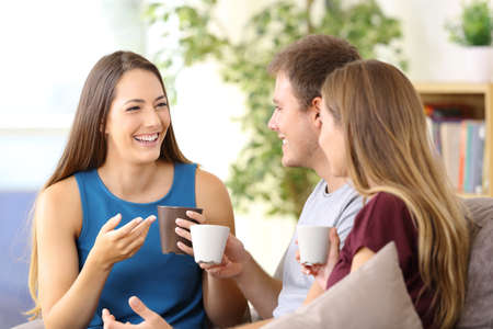 Three happy friends talking and drinking coffee sitting on a couch at home Stock Photo