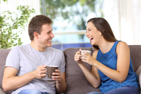 Two people talking and laughing loud sitting on a sofa at home