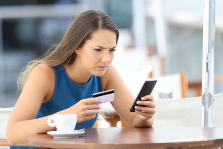 Single worried girl having problems paying on line with a credit card and a phone in a coffee shop terrace