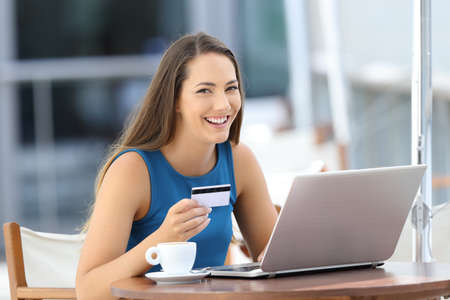 marketing online: Happy buyer using a laptop holding a credit card and looking at you sitting in a bar terrace