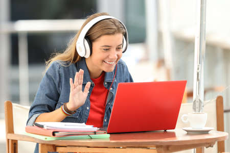 Happy student having a video conference with a red laptop and headphones sitting in a bar terrace Stock Photo