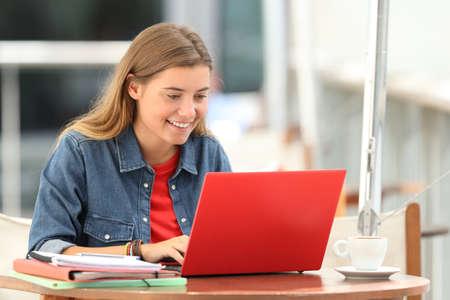 Solo estudiante feliz escribiendo en una computadora portátil sentado en una terraza de la barra Foto de archivo - 85983778