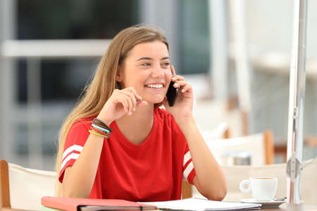 Candid student girl laughing talking on phone siting in a bar terrace