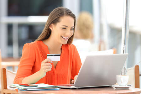 Single woman in orange paying on line with a credit card and a laptop sitting in a restaurant
