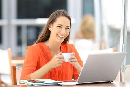 Feliz empresario con una computadora portátil mirando la cámara sentado en una terraza de la barra Foto de archivo - 86084023