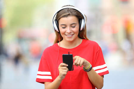 live stream listening: Front view of a single teen girl walking and listening music on the street