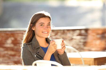 bebes lindos: Chica feliz tomando café y mirando a la cámara sentado en una terraza de la barra en contraluz