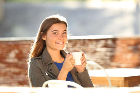 Happy girl drinking coffee and looking at camera sitting in a bar terrace at backlight Stock Photo