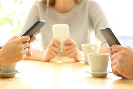 Chiuda in su di tre mani degli amici facendo uso dei loro Smart Phone che si siedono in una barra o in un interno della casa Archivio Fotografico - 86541725