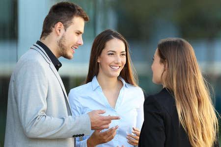 Tre felici dirigenti in piedi a parlare sulla strada con un edificio per uffici in background Archivio Fotografico