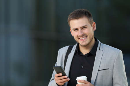 Single happy executive holding a mobile phone and looking at camera on the street