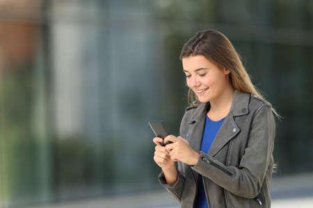 Single fashion teen using a smart phone walking on the street