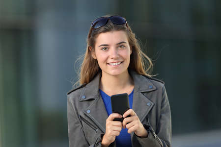 Front view of a fashion girl using a smart phone and looking at you on the street