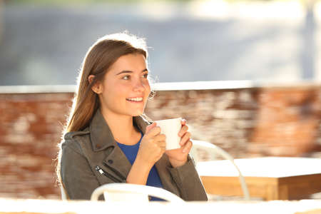 Single happy teen resting and looking away holding a cup sitting in a coffee shop with a warm light in the background