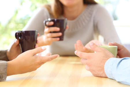 Close up of three friends hands talking and holding coffee cups sitting in a table in a bar or home