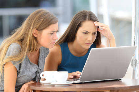 Two worried friends watching media content on line in a laptop sitting in a restaurant terrace