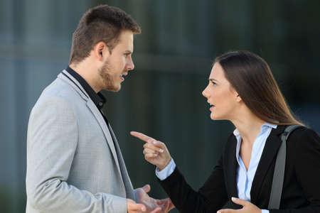 Vista lateral de una pareja enojada de ejecutivos discutiendo de pie en la calle Foto de archivo - 86541741