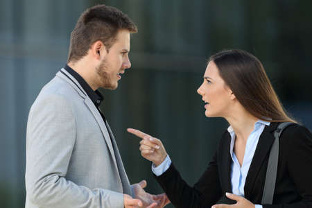 Side view of an angry couple of executives arguing standing on the street Stockfoto