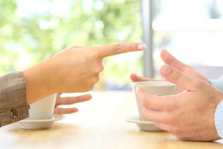 Cerca de las manos de pareja discutiendo sobre una mesa en casa o cafetería