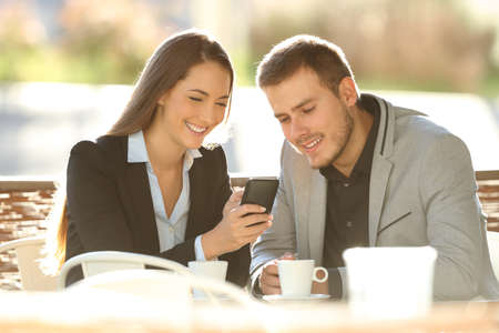 Two happy executives using a smart phone sitting in a restaurant terrace with a warm light in the background