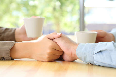 Close up of a couple hands dating and caressing in a bar or home interior Reklamní fotografie