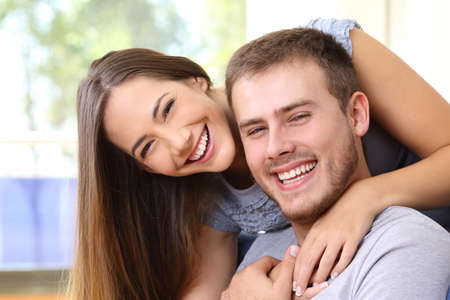 Happy couple smiling together with perfect teeth and looking at camera at home