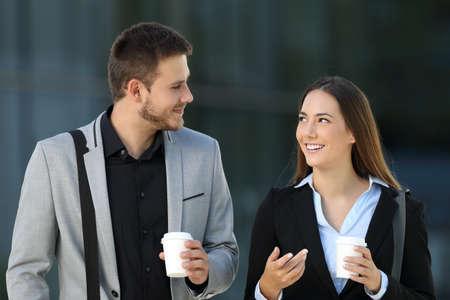 ウォーキングとバック グラウンドでオフィスビルを路上で話す幹部の幸せなカップルの正面図