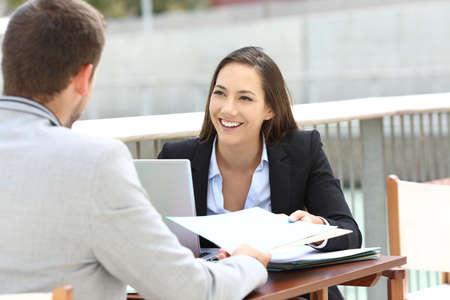 Twee leidinggevenden die werken delen informeert zitten op een barterras Stockfoto
