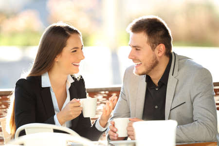 Two executives talking during a cofee break sitting in a bar terrace with a warm backlight Stock Photo