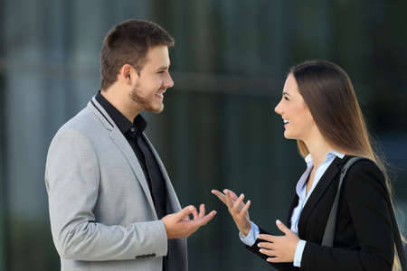Side view portrait of a happy couple of executives talking on the street