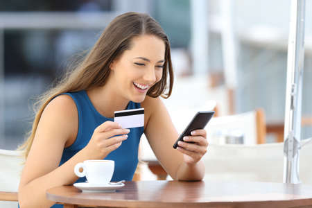 Single happy woman buying on line with a smart phone and a credit card sitting in a bar terrace Reklamní fotografie