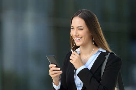 Happy executive talking with earphones during a phone call on the street with an office building in the background