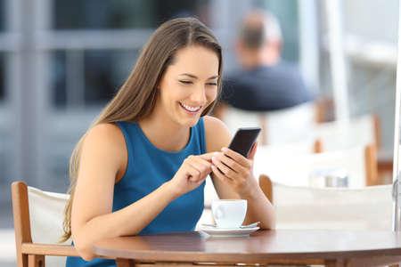 Happy woman using a smart phone alone sitting in a bar terrace Reklamní fotografie