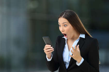 Single excited executive reading amazing news on line in a smart phone on the street Reklamní fotografie
