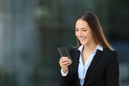 Single smiley executive woman using a mobile phone walking on the street Reklamní fotografie