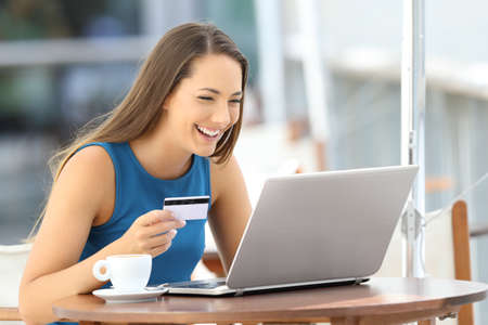 Single happy woman paying on line with a credit card and a laptop sitting in a bar terrace