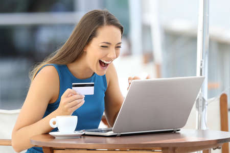 Single excited woman paying on line with a credit card and a laptop sitting in a bar terrace Reklamní fotografie