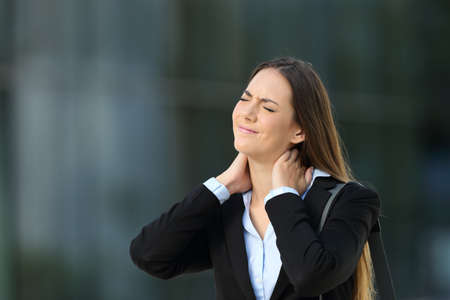 fibromyalgia: Executive suffering neck ache standing alone on the street Stock Photo