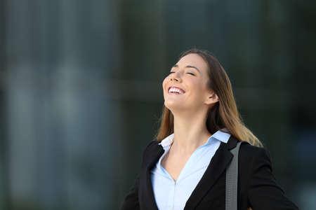 Einzelne glückliche erfolgreiche Exekutive, die tiefe Frischluft auf der Straße mit einem Bürogebäude im Hintergrund atmet Standard-Bild