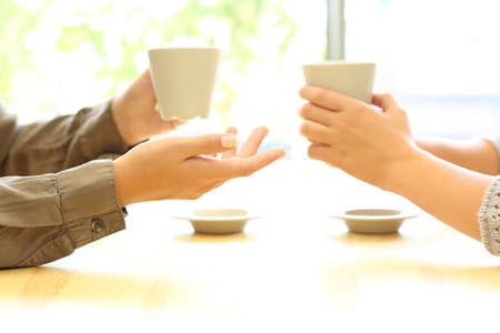 Side view close up of two women hands talking in a bar or house holding coffee cups Reklamní fotografie