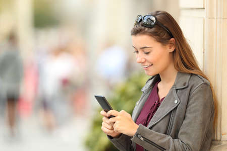 Single fashion girl texting in a smart phone leaning on a building wall outdoors on the street