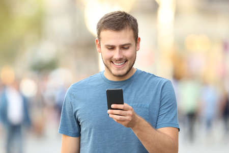 Front view of a happy casual guy checking a smart phone walking outside on the street