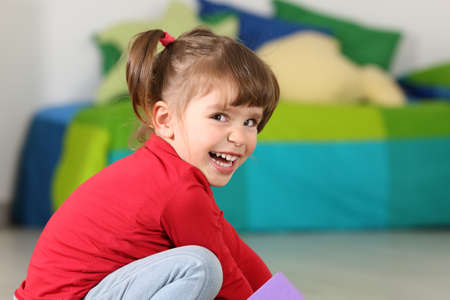 Little toddler girl smiling and looking at camera in her room at home