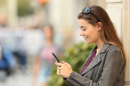 Profile of a fashion girl using a smart phone standing outside leaning on a wall on the street Reklamní fotografie
