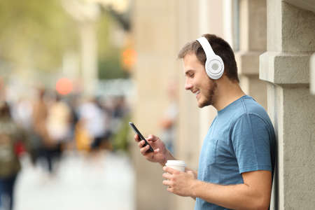 Profile of a happy guy listening music on line with headphones and a smart phone leaning on a wall on the street
